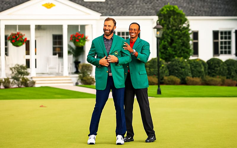 Tiger Woods puts the green jacket on Dustin Johnson after he won the Masters golf tournament at Augusta National Golf Club.